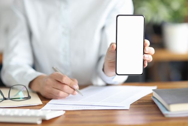 Businesswoman signs contract and holds smartphone with white screen