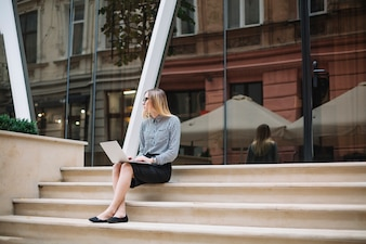 Businesswoman sit at the stairs