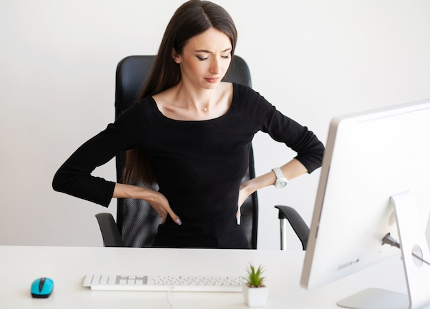 Businesswoman sit in her office and feels pain in back