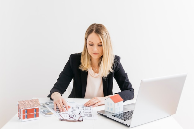Businesswoman siting in front of laptop looking at blueprint at office