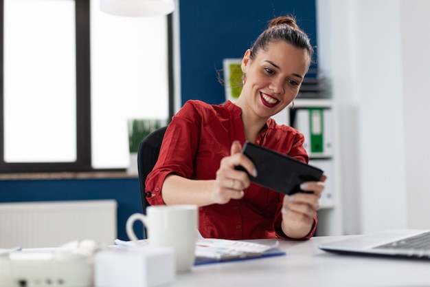 Деловая женщина сидит за столом в корпоративном офисе, играя в видеоигры