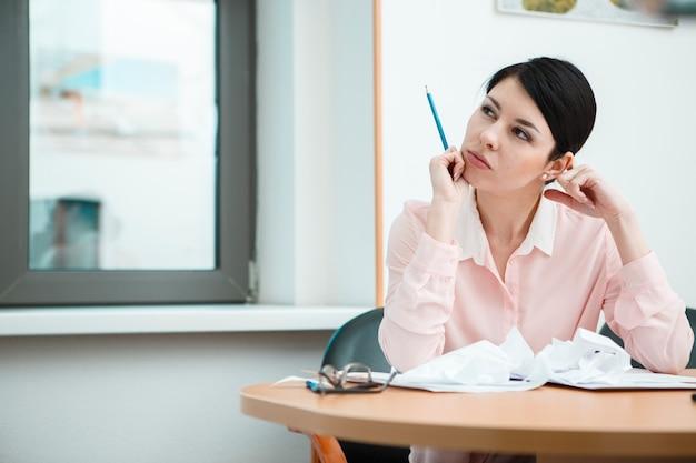 Предприниматель, сидя за столом в офисе в мыслях.