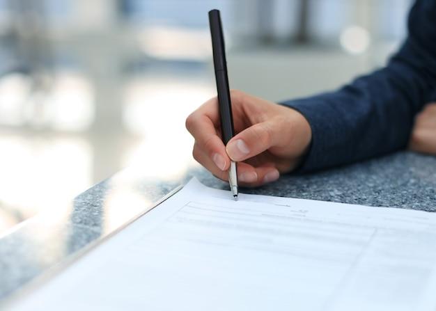 署名に浅い焦点を当てて契約書に署名するオフィスの机に座っている実業家。