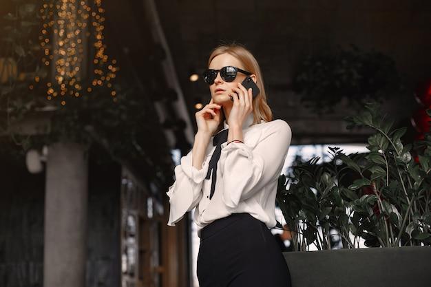 Деловая женщина сидит за столом с телефоном