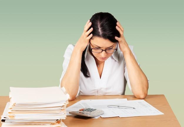 Деловая женщина, сидящая за столом с большим количеством бумаг в офисе