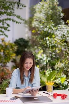Деловая женщина, сидящая за рабочим столом, с помощью планшета и портативного компьютера подключается к интернету в небольшом саду зеленом фоне фона дома. концепция новых нормальных людей и внештатной работы дома.