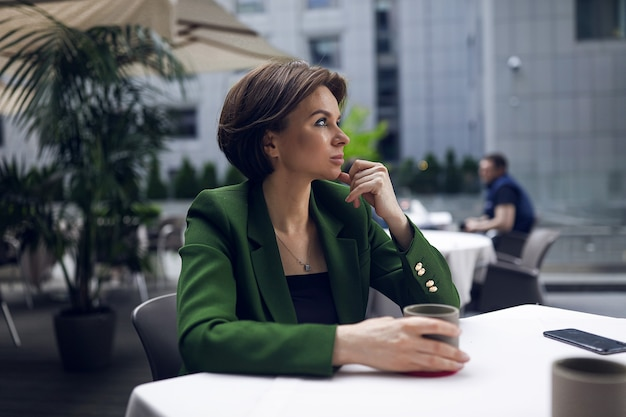 Businesswoman sitting in cafe and having some rest after all meetings and interviews. green stylish jacket and black blouse, short haircut, nude makeup. cup of hot coffee