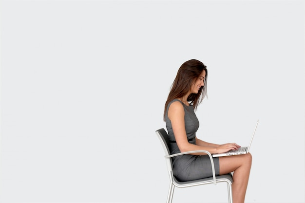 Businesswoman sitting on chair in front of laptop