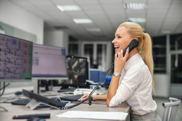 Businesswoman sitting in control room in heating plant and having phone conversation with her boss.