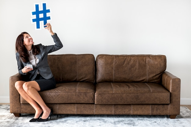 Businesswoman sitting on couch holding icon