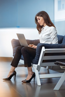 Businesswoman sitting on the couch in the office, typing, looking at pc screen.
