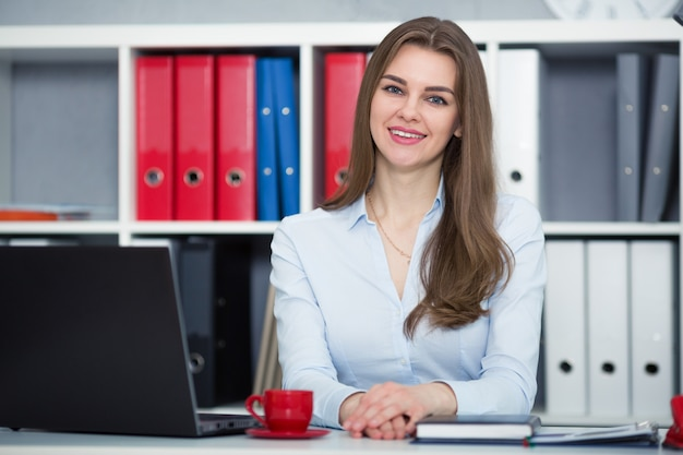 Businesswoman sitting at a desk in the office right shoulder forward. hands on the table. looking into the camera.