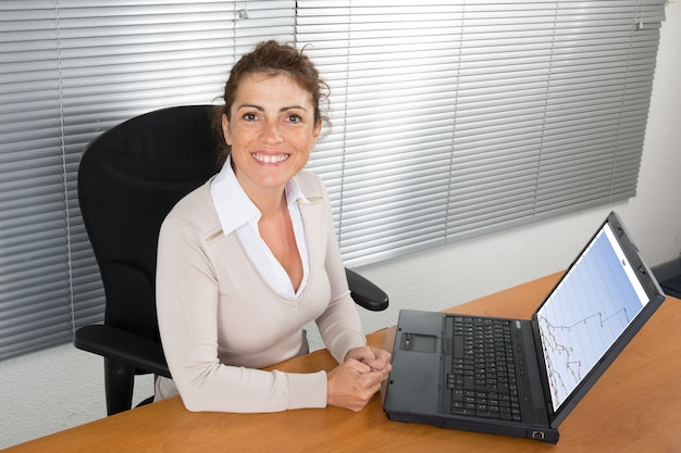 Businesswoman sitting front laptop computer with financial information as graphics and charts on screen
