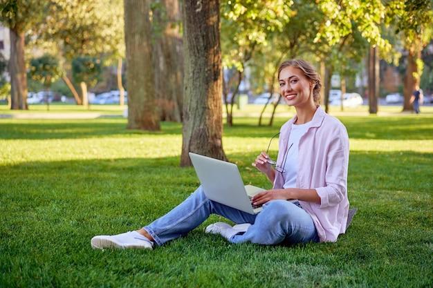 ノートパソコンを使用して草のサマーパークに座っている実業家リモートで作業するビジネスパーソン。アウトドア