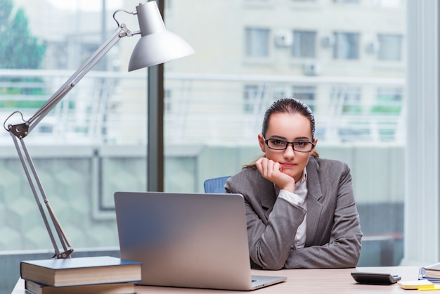 Businesswoman sitting at her desk in business concept