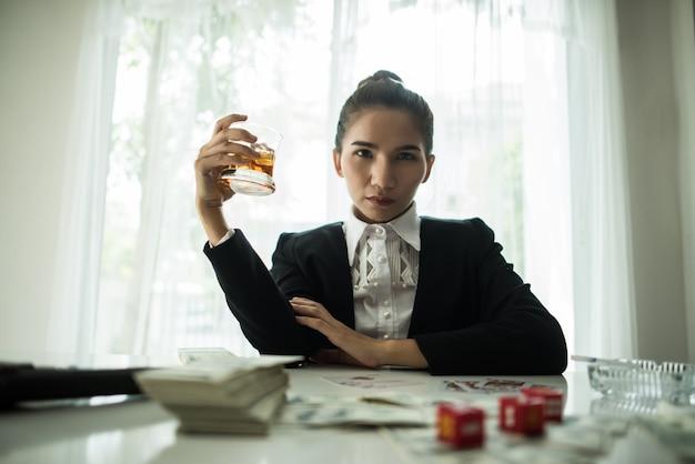 Предприниматель, сидя в бизнес-центре бар, курить сигару и пить виски и деньги на столе