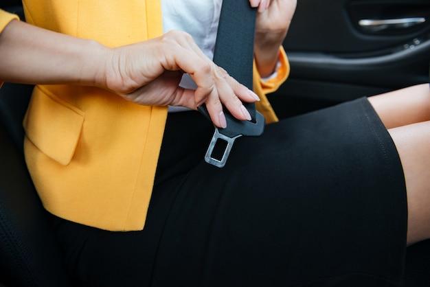 彼女のシートベルトを履いて車に座っている女性実業家