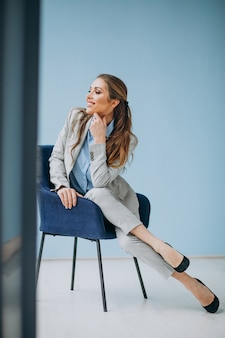 Коммерсантка сидя в стуле на офисе