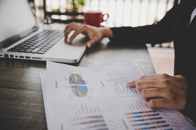 Коммерсантка сидя в столе и работа с компанией финансовых документов