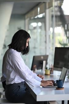 現代のオフィスに座って、レポートを準備するためにコンピューターのラップトップにデータを入力している実業家。