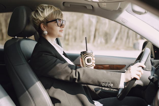 Businesswoman sitting inside a car and drinks a coffee