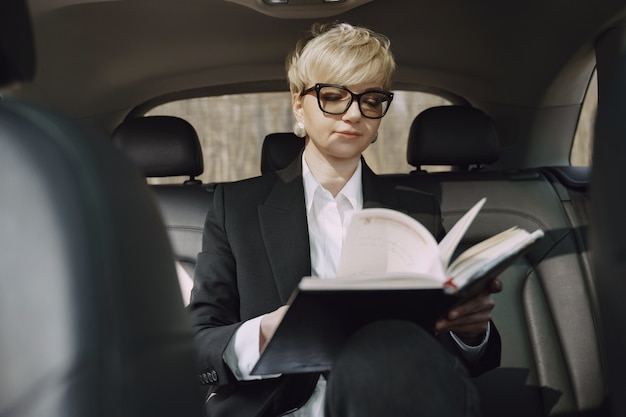 Businesswoman sitting inside a car and use a notebook