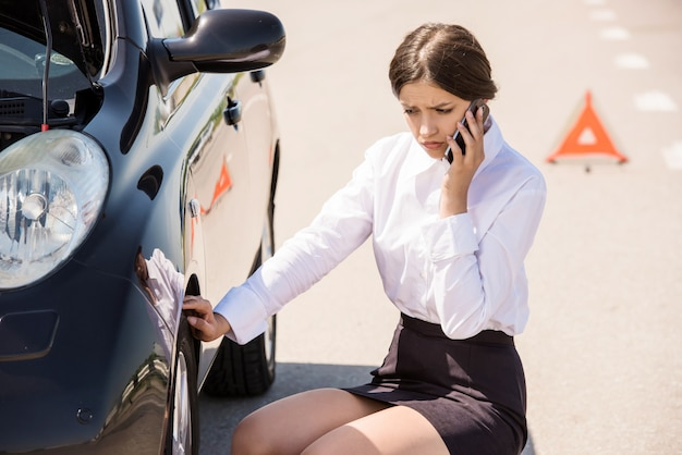 Businesswoman sitting near car and calling for help on phone