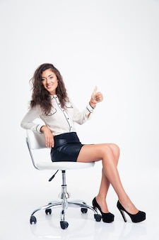 Businesswoman sitting on the office chair and showing thumb up