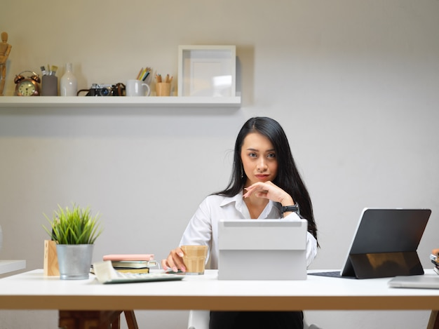 Businesswoman sitting at office desk with coffee