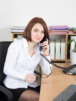 Businesswoman sitting in the office, using phone and holding glasses