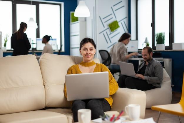 ラップトップを保持しているソファに座って、バックグラウンドで作業している多様な同僚がカメラに微笑んでいる実業家。現代のビジネスオフィシャルで金融会社を立ち上げることについて話している多民族の同僚