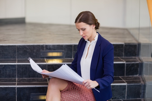 Businesswoman sitting on steps holding blueprint