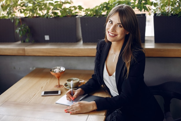 Businesswoman sitting at the table in a cafe and working