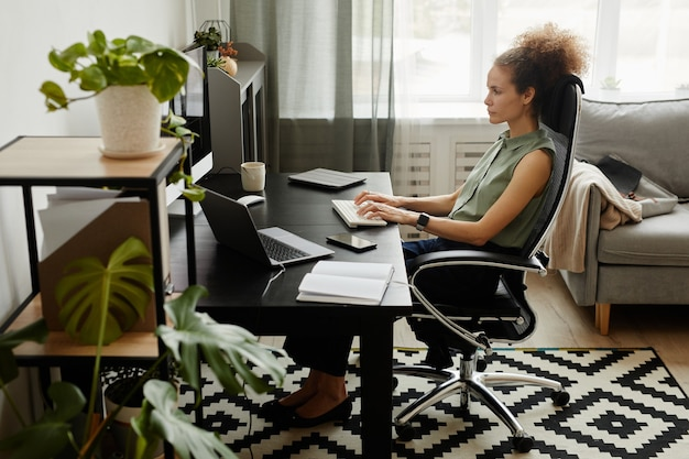 Businesswoman sitting at the table in front of computer monitor and typing on keyboard she working at home