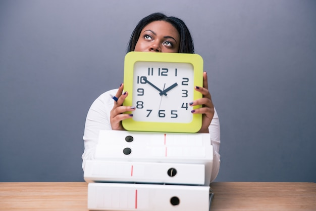Businesswoman sitting at the table with clock
