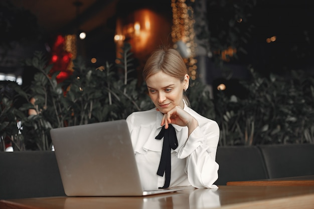 Businesswoman sitting at the table with a laptop