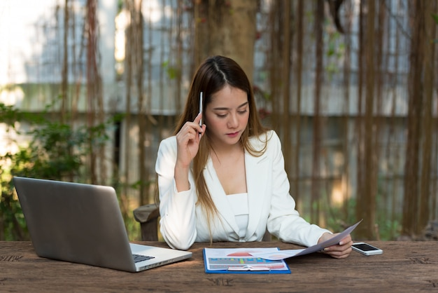 Businesswoman sitting at table with pen and thinking while working at paper sheet beside laptop