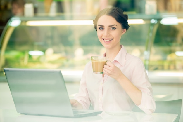 Businesswoman sitting in urban cafe and using laptop.