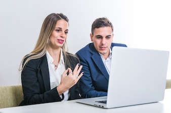 Businesswoman sitting with businessman looking at laptop gesturing