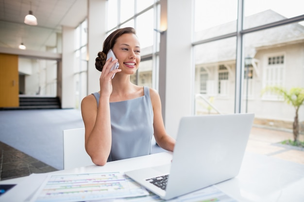 Businesswoman sitting with laptop and talking on mobile phone
