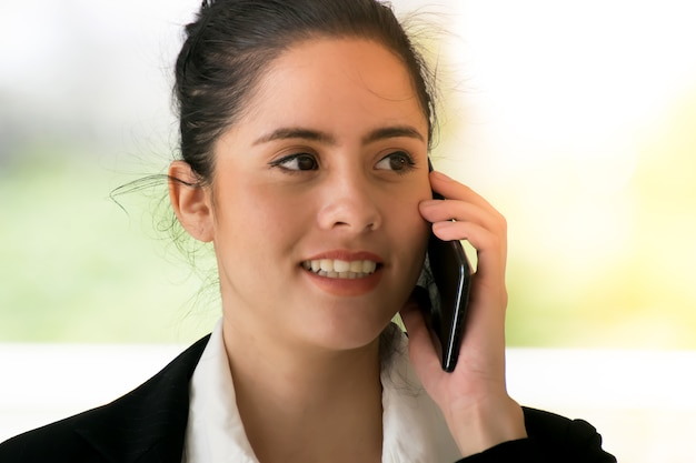 Businesswoman in smart casual using mobile phone outdoors
