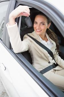 彼女の車で笑顔と鍵を握っているビジネスマン