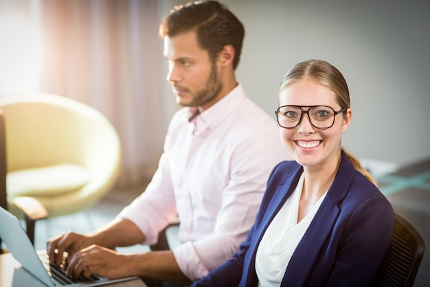 Businesswoman smiling at camera while her colleague using laptop