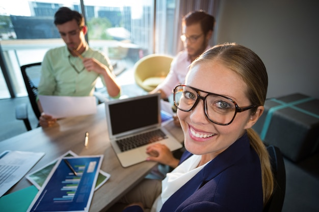 Businesswoman smiling at camera while her colleagues reading document