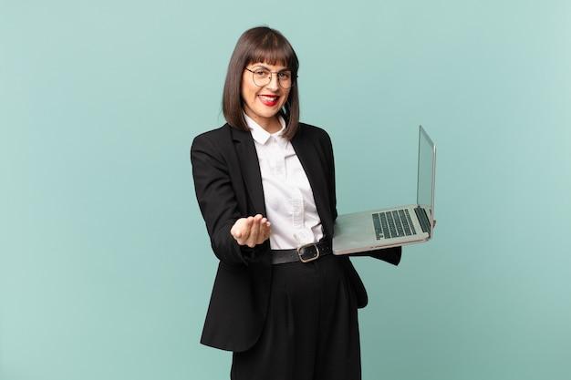 Деловая женщина счастливо улыбается с дружелюбным, уверенным, позитивным взглядом, предлагая и показывая объект или концепцию