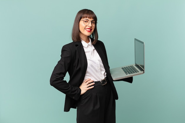 Businesswoman smiling happily with a hand on hip and confident, positive, proud and friendly attitude