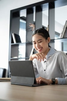 Businesswoman smiling and watching webinar on computer tablet in office.