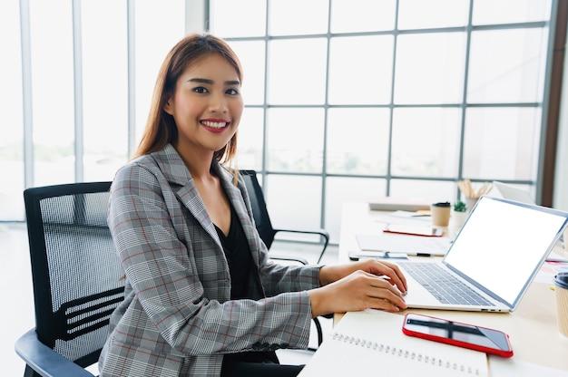 オフィスで働くコンピューターを使用して女性実業家