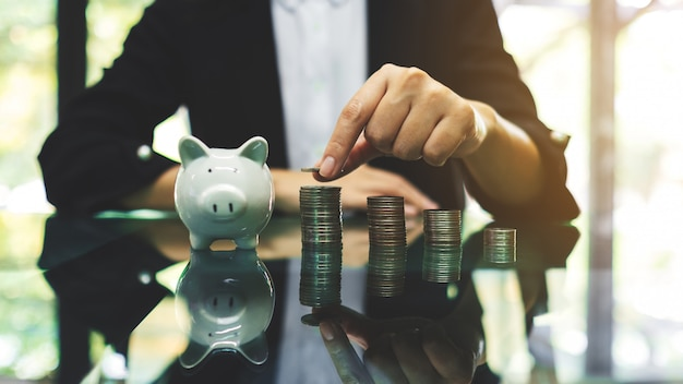 Businesswoman stacking coins with a white piggy bank on the table for saving money and financial concept