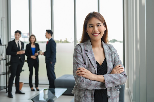 Деловая женщина стоя крест руки и улыбка в офисе